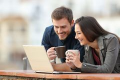 Happy couple checking laptop content on a balcony. Happy couple checking laptop online content holding coffee cups in a balcony with a town in the background stock image
