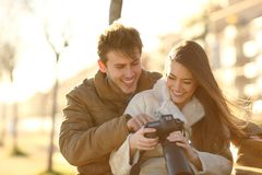 Happy couple checking photos on a dslr camera stock images