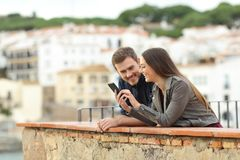 Happy couple checking smart phone in a balcony royalty free stock photo