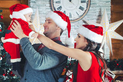 Happy couple and child. Christmas time. Happy couple looking at their child in santa dress Royalty Free Stock Image