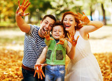 Happy couple with a child in a park in autumn. Hands in the pain Stock Photo