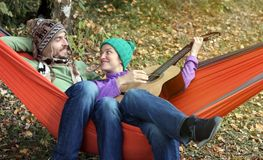 Happy couple chilling in hammock in autumn forest. Woman playing Royalty Free Stock Image