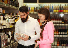 Happy couple chooses alcohol from showcases shop Royalty Free Stock Images