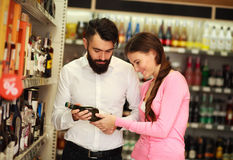 Happy couple chooses alcohol from showcases shop Stock Images
