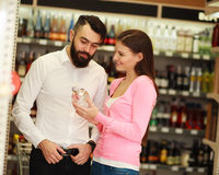 Happy couple chooses alcohol from showcases shop Royalty Free Stock Image