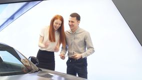 Happy couple chooses first family car to buy in a showroom.  stock footage