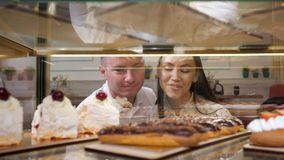 Happy couple chooses tasty cakes in glass show case of shop. Happy young couple chooses tasty fresh cakes standing in glass show case of confectionery shop close stock video
