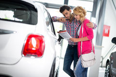 Happy couple chooses to buy a car royalty free stock photo