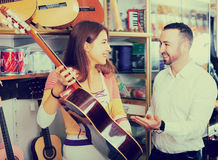 Happy couple choosing acoustic guitar in shop Stock Image