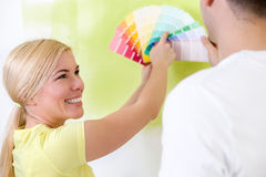 Happy couple choosing colors for painting Royalty Free Stock Image