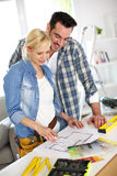 Happy couple choosing colors for walls of house Stock Photos
