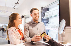 Happy couple choosing engagement ring in mall. Sale, consumerism, shopping and people concept - happy couple with credit card at jewelry store in mall Stock Image