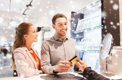 Happy couple choosing engagement ring in mall. Sale, consumerism, shopping and people concept - happy couple with credit card at jewelry store in mall with snow Royalty Free Stock Image