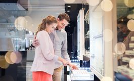 Happy couple choosing engagement ring in mall. Sale, consumerism, shopping and people concept - happy couple choosing engagement ring at jewelry store in mall stock image