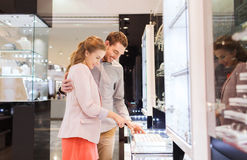 Happy couple choosing engagement ring in mall Royalty Free Stock Photography