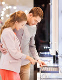 Happy couple choosing engagement ring in mall Stock Images