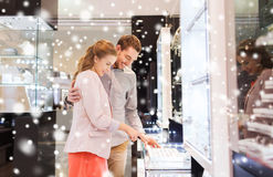 Happy couple choosing engagement ring in mall. Sale, consumerism, shopping and people concept - happy couple choosing engagement ring at jewelry store in mall Royalty Free Stock Photo