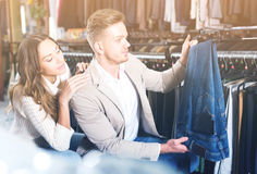 Happy couple choosing new trousers in cloths store Stock Photos