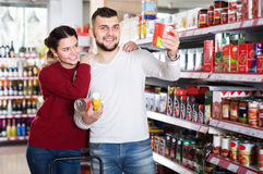Happy couple choosing purchasing canned food for week at superma Royalty Free Stock Images