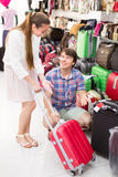 Happy couple choosing suitcase. In the mall and smiling Stock Images