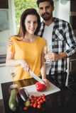 Happy couple chopping vegetables in kitchen Stock Photo