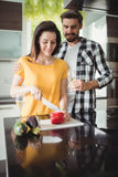Happy couple chopping vegetables in kitchen Royalty Free Stock Images