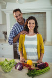 Happy couple chopping vegetables in kitchen stock photos