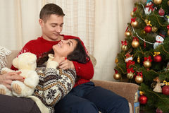 Happy couple in christmas decoration at home. New year eve, decorated fir tree. Winter holiday and love concept. Royalty Free Stock Photo