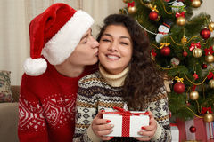 Happy couple in christmas decoration at home. New year eve, decorated fir tree. Winter holiday and love concept. Stock Image