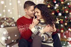 Happy couple in christmas decoration at home. New year eve, ornated fir tree. Winter holiday and love concept. Royalty Free Stock Images