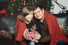 Happy Couple with Christmas and New Year Gift at Home. Royalty Free Stock Images