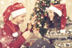 Happy couple with christmas tree and a glass of champagne at home. Winter holiday and love concept. Yellow toned with snow. Royalty Free Stock Image