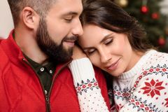 Happy couple at christmastime. Beautiful happy young couple embracing at christmastime royalty free stock photography