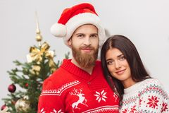 Happy couple at christmastime. Beautiful happy young couple smiling at camera at christmastime stock image