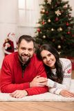 Happy couple at christmastime. Cheerful young couple lying on carpet and smiling at camera at christmastime stock images
