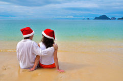 Happy couple in chtistmas hats on tropical beach Stock Images