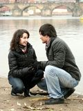 Happy Couple in the City. A young couple - a man and a woman together near the river, both smiling; wearing winter jackets; cold weather Stock Image