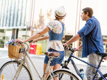 Happy couple in city with bike. Happy young couple in city with bike Stock Photos