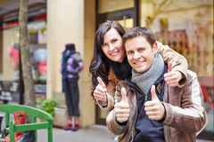 Happy couple in city holding thumbs Stock Photos
