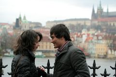 Happy Couple in the City - Prague. A young couple - a woman and a man talking intimately; wearing winter jackets; the Prague Castle in the background Royalty Free Stock Photography