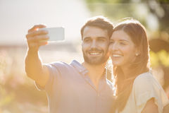 Happy couple clicking selfie with smart phone Stock Photography