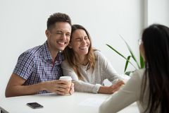 Happy couple clients laughing planning to sign contract at meeti. Happy couple clients laughing at funny joke meeting realtor, mortgage insurance broker or stock photography
