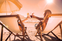 Happy couple clinking their glasses while relaxing on their deck chairs Stock Images