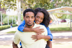 Happy couple. Closeup portrait of a young couple,guy giving women piggy back ride, happy moments, positive human emotions on  outdoors outside park background Stock Image