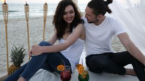 Happy couple with cocktails, have fun, bungalow with white cloth, an exotic vacation, on background tropical fruits. Happy couple with cocktails, have fun in stock video