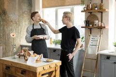 Happy couple with coffe at home kitchen. Handsome homosexual mens drinking coffe. And feeding each other with cookies royalty free stock photos