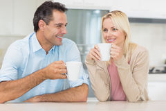Happy couple with coffee cups in kitchen Royalty Free Stock Photos