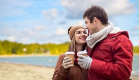 Happy couple with coffee cups over autumn beach stock photography