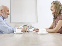 Happy Couple With Coffee Cups Reading Magazine Stock Image