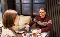 Happy couple with coffee eating cake at cafe Stock Photo